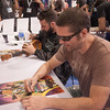 """Jim Mahfood signing a ukelele and Joe Casey signing a poster for their comic book """"Miami Vice"""" by Sonia.Harris"""