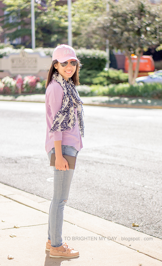 pink cap, navy floral scarf, lilac purple sweater, gray taupe clutch, light wash jeans, pink boat shoes