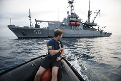 In this file photo, an Explosive Ordnance Disposal Mobile Unit Sailor guides a rigid-hull inflatable boat to USNS Safeguard (T-ARS 50) during search and survey operations of the sunken World War II navy vessels USS Houston (CA 30) and HMAS Perth D29) in Indonesia's Banten Bay in October 2015. (U.S. Navy/MC2 Arthurgwain L. Marquez)