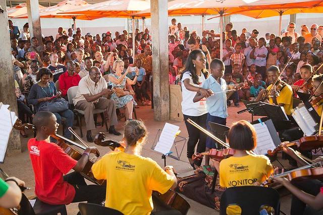 Yksi onnekas pääsi johtamaan orkesteria, kun alakoululaiset, opetusministeri ja Suomen suurlähettiläs kuuntelivat Xiquitsi-orkesterin ja kuoron esitystä lokakuussa 2015 Maputossa.