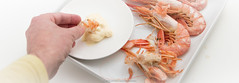 Human hand putting prawn meat in mayonnaise. Serve…