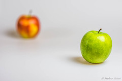 Green apple in the foreground, red apple in the ba…