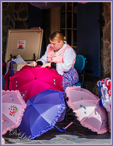 Image of a lady painting the parasols at the Magic Kingdom