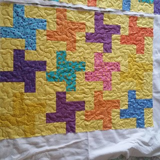 Scrappy twirl quilt is quilted.