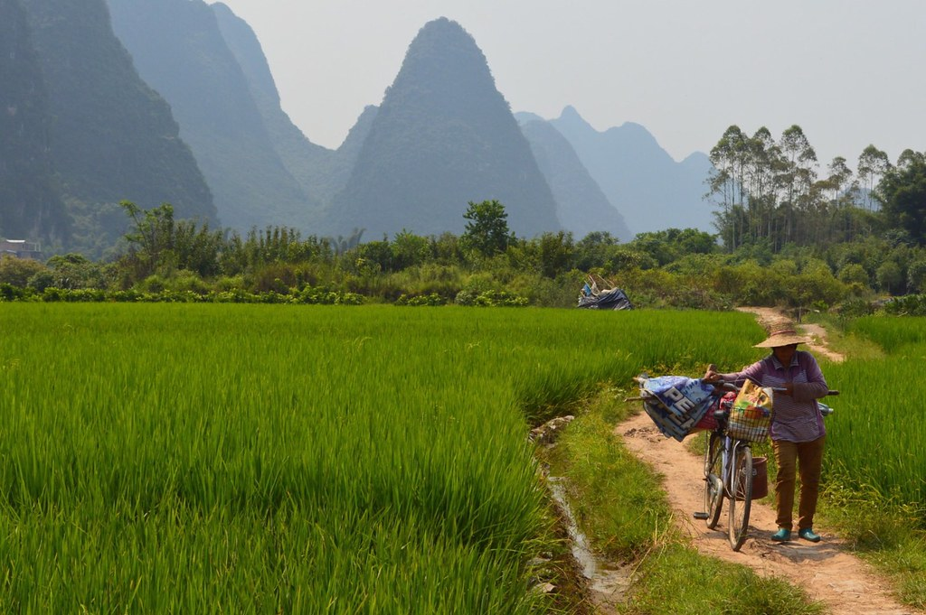 Yulong River area with a local walking her bicycle