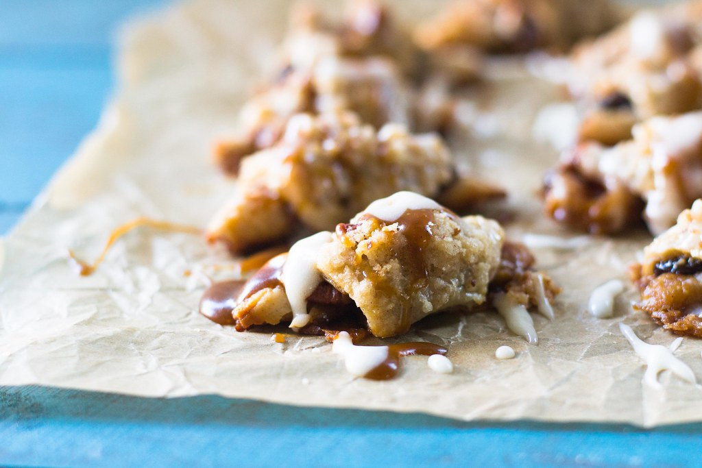 Sticky bun, meet Rugelach! A twist on the traditional Jewish cookie, these rugelach are filled with caramelized nuts and topped with streusel and drizzled with sweet caramel. #rugelach #cinnamonbun