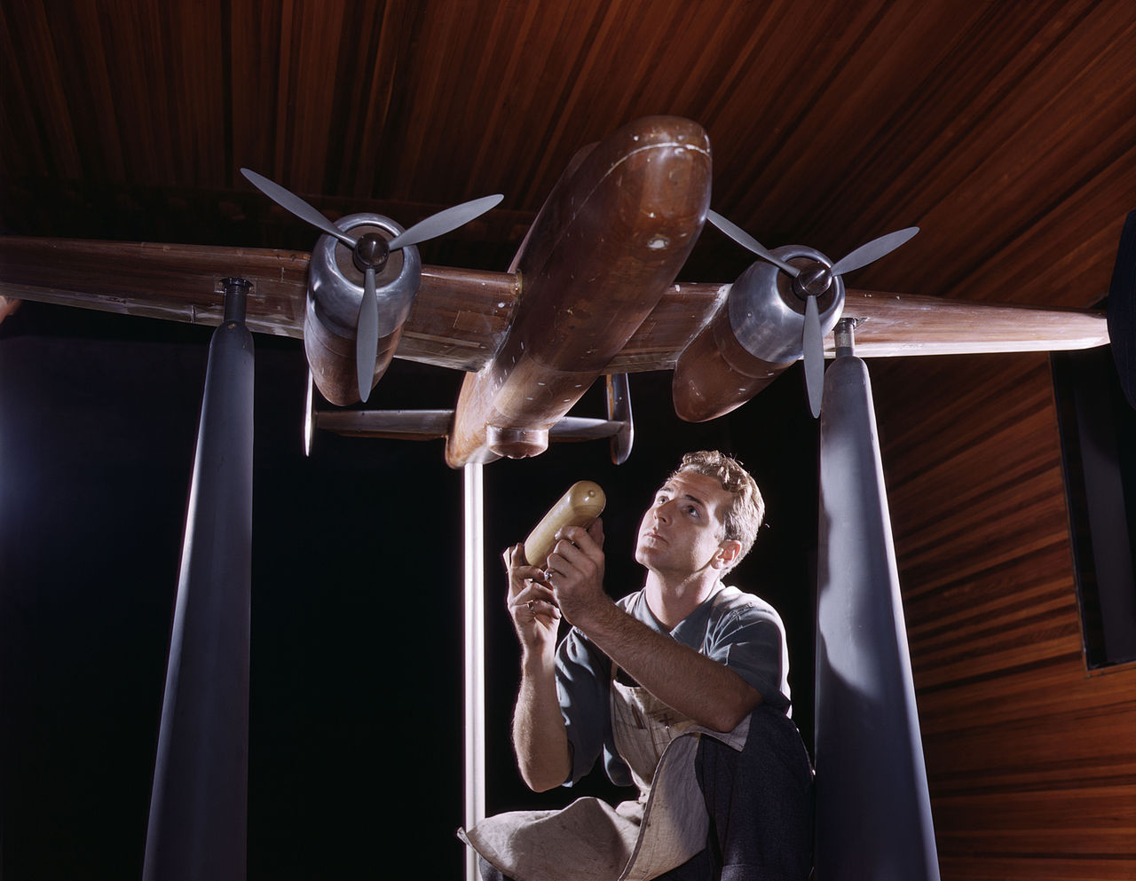 An experimental scale model of the B-25 plane is prepared for wind tunnel tests in the plant of the North American Aviation, Inc, Inglewood, Calif, The model maker holds an exact miniature reproduction of the type of bomb the plane will carry.