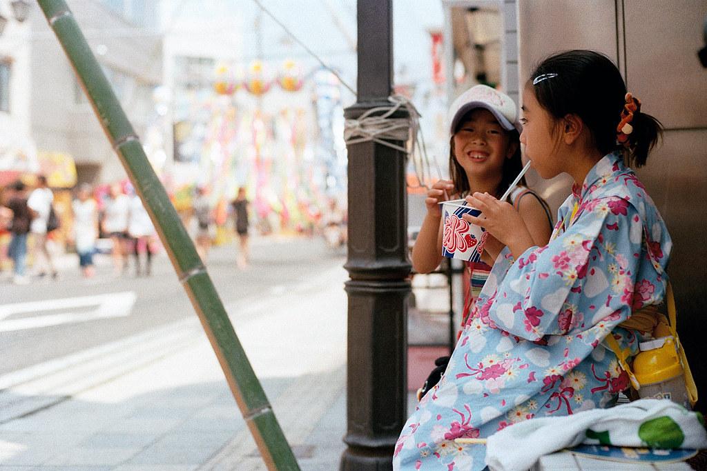"""七夕祭 Iwaki (いわき市 Iwaki-shi), Fukushima 2015/08/06 在路旁休息吃冰,那時候我正好在換新的底片,一換好馬上蹲在旁邊拍她們。  Nikon FM2 / 50mm Kodak ColorPlus ISO200  <a href=""""http://blog.toomore.net/2015/08/blog-post.html"""" rel=""""noreferrer nofollow"""">blog.toomore.net/2015/08/blog-post.html</a> Photo by Toomore"""