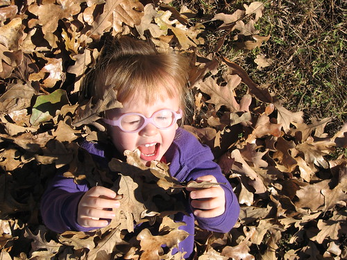 Kaitlyn playing in pile of dry leaves