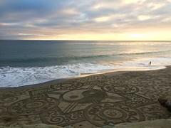 Sunset over a sculpted beach.