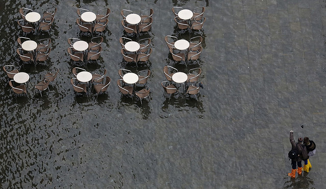 People take a selfie on St. Mark's Square, flooded during a period of seasonal high water, on the first day of Carnival in Venice, Italy, on February 1, 2015.