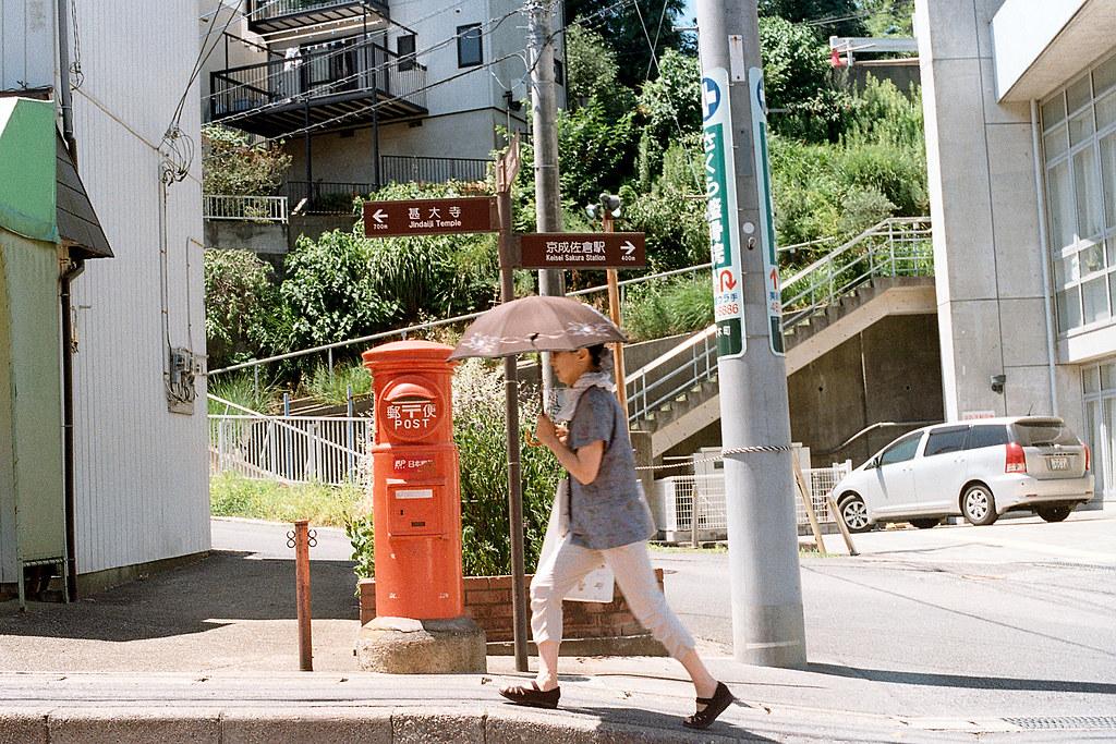 """千葉県佐倉市 さくらし 郵便 2015/08/05 在這條一路上坡的路上有個很顯眼的郵筒,我有拍一張沒有人經過的畫面,可是後來想想這樣的畫面太過孤單了,一路上都提醒自己要記得把人放進去,當地人的生活也是這地域的一部分。所以我在這裡等了一張有人的畫面。  Nikon FM2 / 50mm Kodak ColorPlus ISO200  <a href=""""http://blog.toomore.net/2015/08/blog-post.html"""" rel=""""noreferrer nofollow"""">blog.toomore.net/2015/08/blog-post.html</a> Photo by Toomore"""