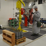 A munitions handler uses a lift assist to move monitored, reconfigured and inspected 105mm agent-filled projectiles from the conveyor onto a pallet. The palletized munitions are returned to the U.S. Army Pueblo Chemical Depot for storage to await destruction at the Pueblo Chemical Agent-Destruction Pilot Plant.