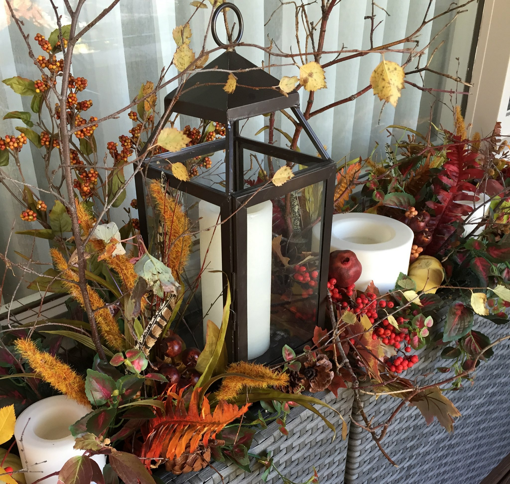 Autumn outdoor decorating with candles, twigs and berries