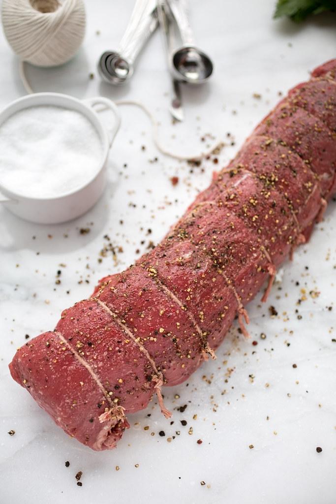 Seasoned beef tenderloin on a marble board