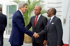 With Haitian President Michel Martelly looking on, U.S. Secretary of State John Kerry is greeted by Haitian Prime Minister Evans Paul before his meeting with the President and Prime Minister at the Presidential Palace in Port-au-Prince, Haiti, on October 6, 2015. [State Department photo/ Public Domain]