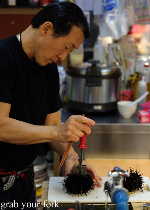 Opening fresh sea urchin at Hakodate Morning Market, Japan