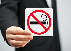 man in suit holding no smoking sign