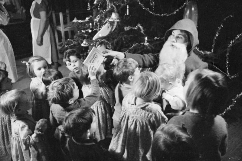 Father Christmas hands out toys and games, including a set of building bricks, to children at a home for evacuees in Henley-on-Thames, 1941