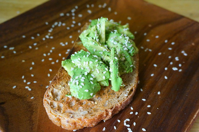 Avocado toast - now with sesame seeds! They're scattered over the top of the toast itself, and on the wooden plate below