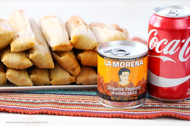 Chipotle Chicken Tamales stacked up on a plate with a can of La Morena peppers and a can of coca cola.