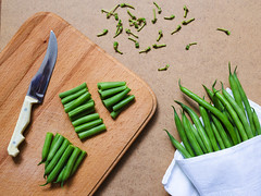 Sliced green beans  and a bunch of green beans on the table with a napkin and knife