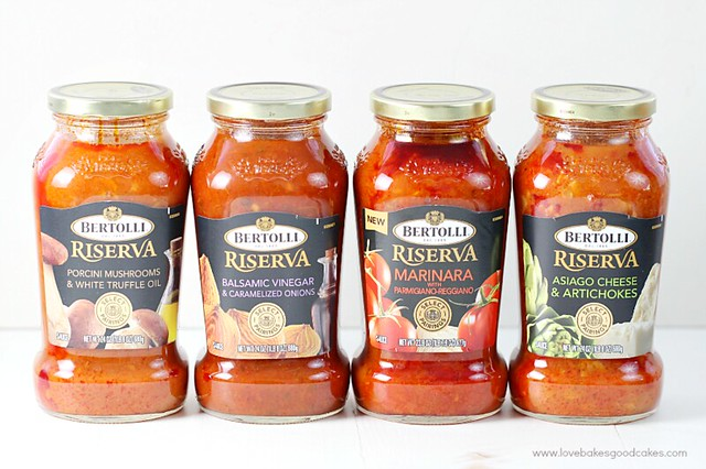 Four jars of Bertolli Sauce with different flavors.