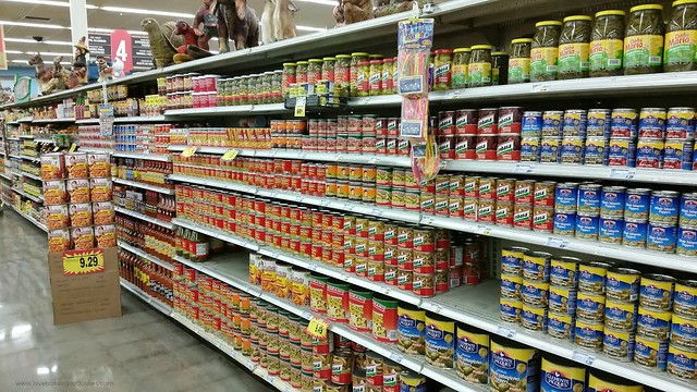 A grocery store isle with canned goods on the shelf.