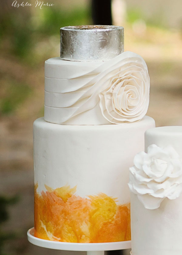 the medium sized cake features a handpainted water color base with a fondant swirl tier and topped with silver leafing