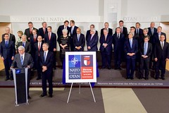 U.S Secretary of State John Kerry, his fellow Foreign Ministers, and North Atlantic Treaty Organization Secretary General Jens Stoltenberg listen as Polish Foreign Minister Witold Waszczykowski discusses the logo of next year's NATO Summit Meeting in Warsaw, Poland, during a break at a NATO Ministerial meeting on December 1, 2015, at NATO Headquarters in Brussels, Belgium. [State Department photo/ Public Domain]