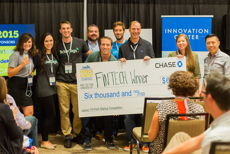 FamZoo CEO Bill Dwight (middle of check) holds first prize award for FinCon15 FinTech Startup Competition