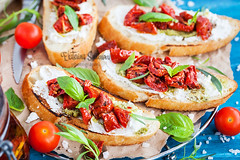 Bruschetta with cream cheese, pesto, fresh basil a…
