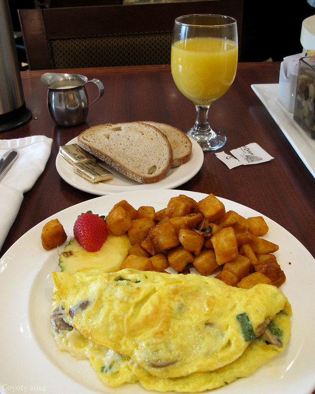 Omelet with hash browns, fruit, bread, and orange juice