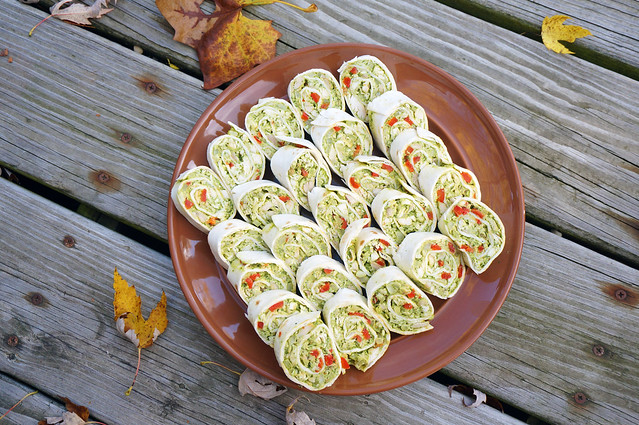 Cilantro chicken pinwheels laid out in overlapping rows on a brown plate, sitting on weathered with a scattering of autumn leaves