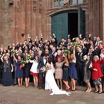 Hochzeitskuss für die Kamera bejubelt von den Hochzeitsgästen vor dem Haupteingang der Bernharduskirche.