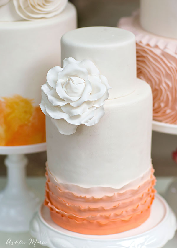 the smallest of the three cakes is simply beautiful with a double barrel base with ombre ruffles topped with a gumpaste white rose