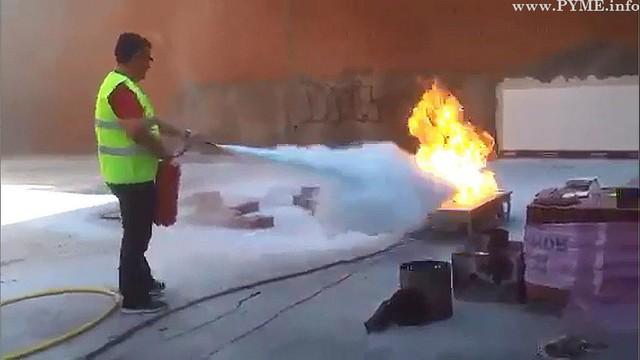 Un alumno del Curso de Prevención de Riesgos Laborales de CONFAES para profesionales de la construcción, apaga un fuego.