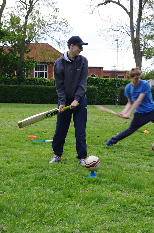 Man swinging a cricket bat at ball on tee