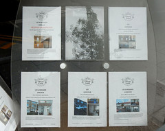Five sheets of A4 paper mounted in a perspex stand, each listing details of a house or flat that has been let and/or managed by Oliver Gold.