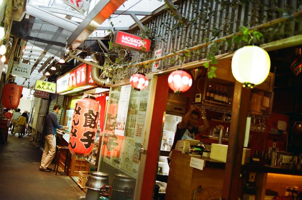 吉祥寺 Tokyo, Japan / Kodak ColorPlus / Nikon FM2 其實我是想要拍遠一點的餃子燈籠,但當我按下快門後才注意到原來酒吧的店員也在我的鏡頭內。  當我注意到後,只好禮貌的點頭,希望他不會介意。  還好他也點頭微笑。  Nikon FM2 Nikon AI AF Nikkor 35mm F/2D Kodak ColorPlus ISO200 0995-0013 2015/10/01 Photo by Toomore