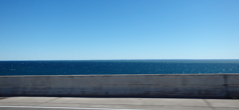 the lake out to the horizon, with the highway guardrail in the foreground