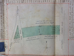 "A hand-drawn plan showing a long, rectangular, green-shaded area of land.  Two roads meet in a point on the left-hand side, and on the right-hand side is another road labelled as the ""Turnpike Road"" from Croydon to London.  A narrow edge of the green area fronts on this road, and three houses have been drawn here in pencil."
