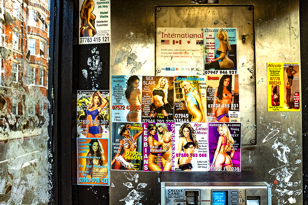 Sex ads in phone booth--London