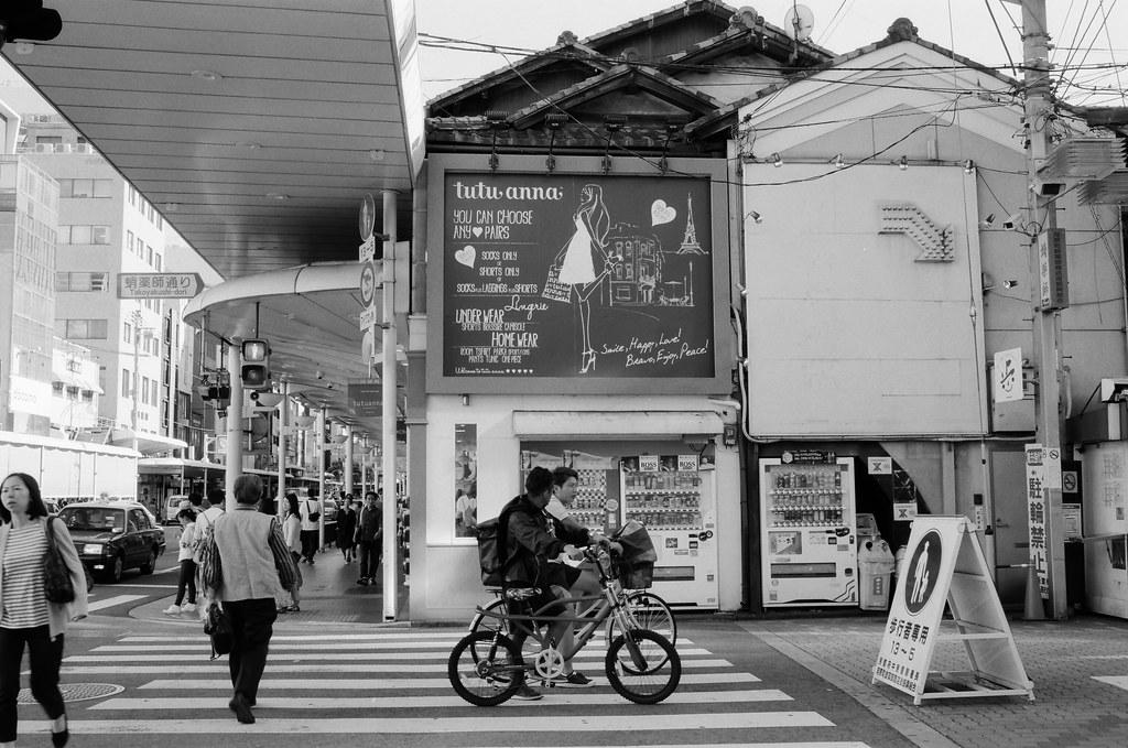 四条通 京都 Kyoto 2015/09/29 後來我走到四条通與新京極那個路口,那時候我肚子很餓,附近剛好有一間可以刷卡消費的店(因為身上現金快不夠用),就進去吃了鮭魚丼飯!  他們一直在路中間聊天!  Nikon FM2 Nikon AI AF Nikkor 35mm F/2D Kodak 100TMax 1273-0012 Photo by Toomore
