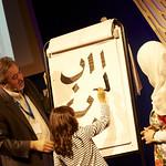Haji Noor Deen | Haji Noor Deen works with a young audience member to create beautiful calligraphy © Helen Jones