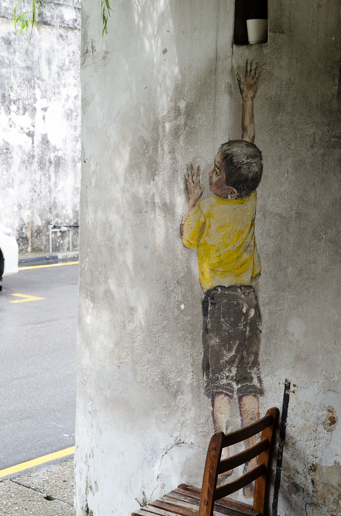 Famous Penang mural arts - The boy on chair, trying to reach something.