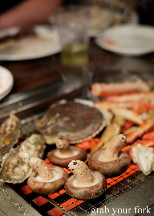 Grilled mushrooms, live oysters, live scallops and king crab at Nanda all-you-can-eat buffet in Sapporo