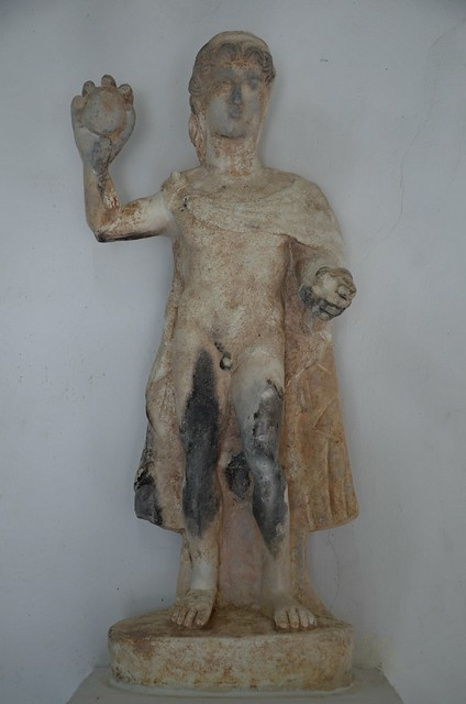 Statue of a youth wearing a cloak and holding two balls in his left hand and one in his upraised right hand, perhaps representing a man playing the trigon ball game, Roman period, found at the Apollo Hylates sanctuary, Kourion Museum, Cyprus