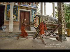 Young monk beats a temple drum to signify call to prayer at Kampong Phluk, Siem Reap, Cambodia