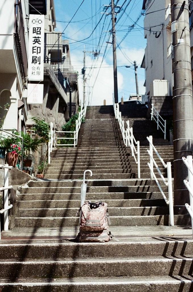 長崎 Nagasaki 2015/09/09 最後一天在長崎,要搭客運到長崎空港搭飛機到關西空港。在尾道拿到的雨傘一路就這樣從廣島、福岡、熊本帶到長崎。找一個好場景和我的背包一起紀錄。  Nikon FM2 Nikon AI Nikkor 50mm f/1.4S Kodak UltraMax ISO400 Photo by Toomore